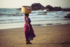 GOA, INDIEN - 4. MÄRZ: Frau in den Sari mit Korb auf ihrem Kopf wal Stockbild