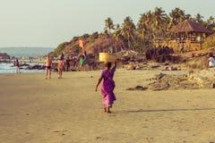 GOA, INDIEN - 4. MÄRZ: Frau in den Sari mit Korb auf ihrem Kopf wal Lizenzfreie Stockfotografie