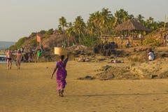 GOA, INDIEN - 4. MÄRZ: Frau in den Sari mit Korb auf ihrem Kopf wal Lizenzfreies Stockbild