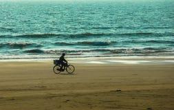 GOA, INDIEN, AM 5. MÄRZ 2011: Radfahrer, der auf Sand auf einem Hintergrund der Indische Ozean geht Lizenzfreie Stockbilder