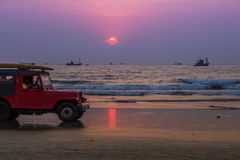 GOA, INDIEN - 1. MÄRZ: Roter Autojeep mit Rettern auf Arambol-beac Stockfotos