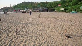 GOA INDIEN - MARS 2013: pojkar som spelar strandfotboll lager videofilmer