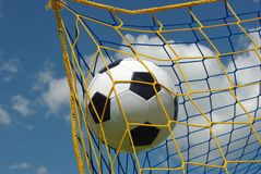 Goal. The foot ball in mesh of goal on background of clouds Stock Images