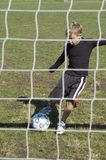 At the goal. Looking through the net at Soccer player kicking the ball at the goal Royalty Free Stock Images