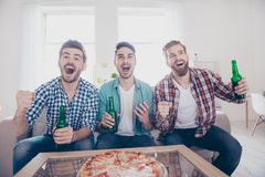 Goal! Cheerful young guys are watching match on couch at home an. D drink beer, eat pizza on the sofa at home indoors. They are fans of sports games as football royalty free stock image
