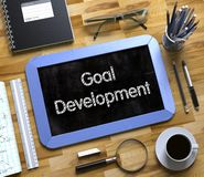 Goal Development - Text on Small Chalkboard. 3D. Small Chalkboard with Goal Development. Top View of Office Desk with Stationery and Blue Small Chalkboard with Stock Images