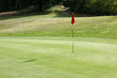Goal Flag on the green. This image is of the goal you want to  obtain while playing golf. It represent the end of that hole; represent the goal you want to Royalty Free Stock Images