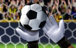 Goal keeper saving a ball with spectator in background Royalty Free Stock Images
