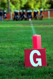 Goal Line. Sign for American Football.  A team of players is visible in the blurred background.  There is green grass and dappled sunshine Stock Image