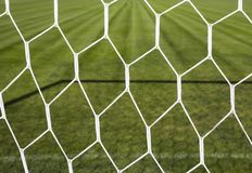 Goal net and green soccer pitch. On sunny day Stock Images