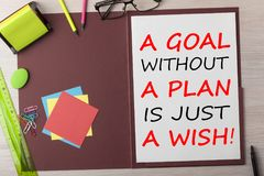 A Goal without a Plan is Just a Wish Concept. A Goal without a Plan is Just a Wish written in paper sheet on presentation folder and various stationery on wooden stock photography