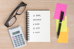 A goal without a plan is just a wish. Motivational handwriting on a open notebook with calculator, eye glasses and pen on wooden desk Royalty Free Stock Photography