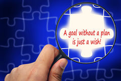 A goal without a plan is just a wish! word. Magnifier and puzzle Royalty Free Stock Photo