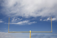 Goal Post. Yellow football goal post with clouds in the sky Stock Photo