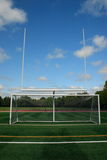 Goal Post and Soccer Net. A football goal post and soccer net with bright blue sky and green grass Stock Images