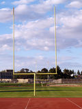 Goal posts empty football field clouds Royalty Free Stock Images