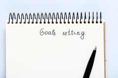 Goal setting. In notepad with pen on grey background stock photo