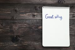 Goal setting. In notepad on wooden table stock image
