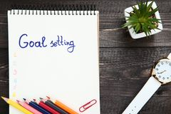 Goal setting in notepad. With colorful pencils, wrist watch and green plant on wooden table royalty free stock images
