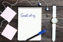 Goal setting in notepad. With earphones, wrist watch and pen on wooden table stock photography