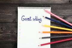 Goal setting in notepad. With colorful pencils on wooden table royalty free stock images