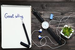 Goal setting in notepad. With earphones, wrist watch and green plant on wooden table stock image