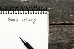 Goal setting in notepad. With pen on wooden table stock photography