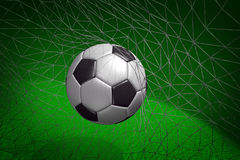 Goal. Soccer ball in goal net with green field background Stock Photo