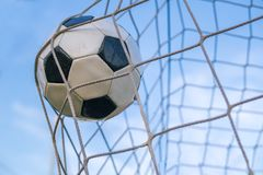Goal - soccer or football ball in the net against blue sky.  Royalty Free Stock Photo