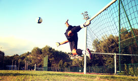 Goal stop a ball. Goalkeeper jumping to stop a ball stock photo