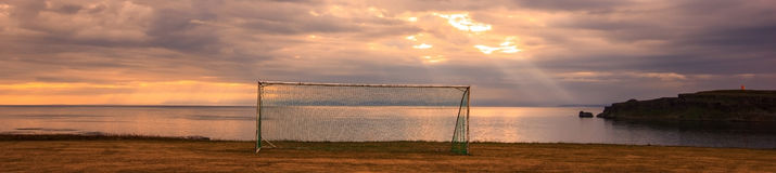 A goal with sunlight shining through clouds at dawn as a background. Concepts of making lots of effort and then be successful Stock Photos