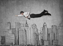Goal is the top of the sky. Man 'flying' over an illustrated city Royalty Free Stock Photos