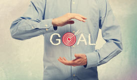 Goal. Young man in blue shirt holding a concept of goal stock photography