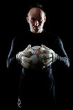 Goalie on black. Portrait of football goalkeeper on black background. Man is wearing goalie gloves and goalkeeper's blouse Royalty Free Stock Photo