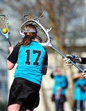 Goalie blocking LAX player. High School girls varsity lacrosse goalie blocking a shooter Stock Images