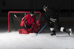 Goalie do hóquei de gelo com os skateres que disparam no disco fotografia de stock