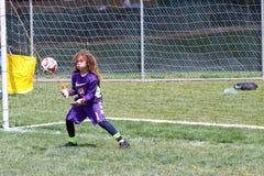 Goalie för ungdomfotbollfotboll som fångar bollen Duing en lek Arkivbild
