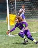 Goalie för ungdomfotbollfotboll som går för räddningen Arkivfoto