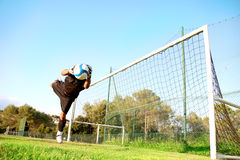 Goalie stops a ball. Goalkeeper diving to stop the soccer ball royalty free stock images