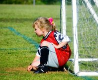 Goalie Watching and Waiting. Cute young goalie waiting by the net for the game to start royalty free stock image