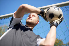 Goalkeeper with ball at football goal on field Royalty Free Stock Image