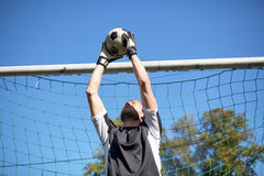 Goalkeeper with ball at football goal on field Royalty Free Stock Photos