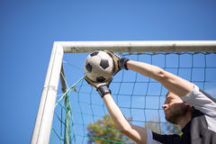 Goalkeeper with ball at football goal on field Stock Images