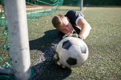 Goalkeeper with ball at football goal on field Royalty Free Stock Photo