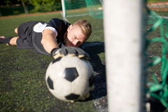 Goalkeeper with ball at football goal on field Stock Photo