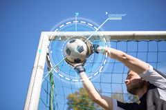 Goalkeeper with ball at football goal on field. Sport, technology and people - soccer player or goalkeeper catching ball at football goal on field Stock Photography