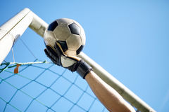 Goalkeeper with ball at football goal over sky Stock Photography