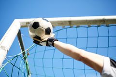 Goalkeeper with ball at football goal over sky Stock Image