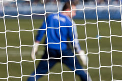 Goalkeeper behind football net Stock Photo