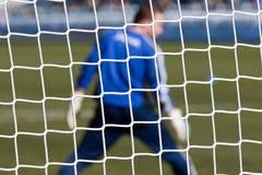 Goalkeeper behind football net stock photo